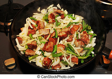 Frying meat with vegetables on black cast- iron pan