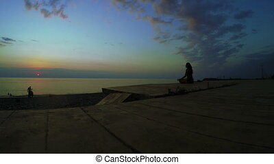 Yoga at sunset -  Girl in lotus position on sea sunset