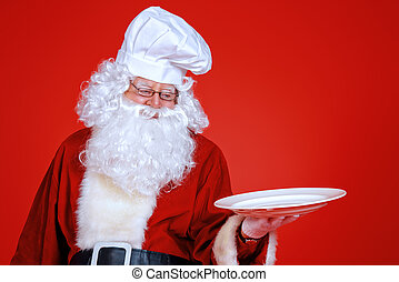 oldman happy - Jolly Santa Claus in a chefs hat holds a...