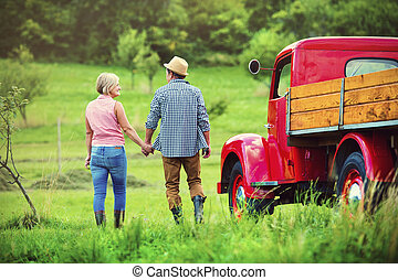 Couple with red truck - Senior couple walking by a red truck...