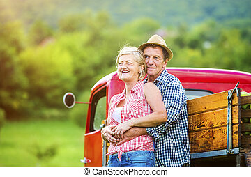 Couple with red truck - Senior couple standing next to the...