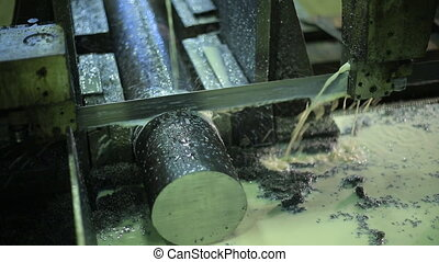 Machine with metal band saw. Cutting thick bar iron in metalworking. slow sawing thick piece of pure metal using an oil-based lubricant, and emulsions.