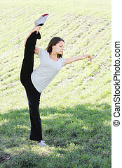 Vertical split outdoors - Young woman makes vertical split...