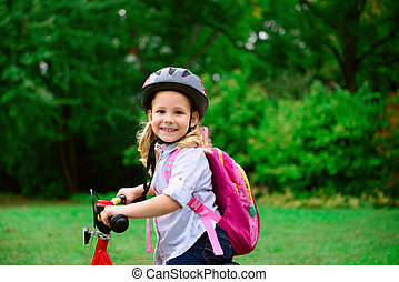 Pretty little girl ride with bicycle in summer park