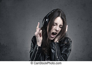 young Woman with head phones listening to music and Singing...