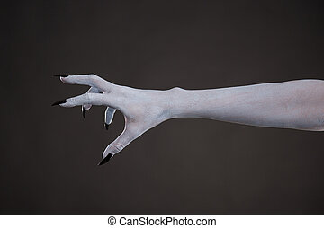 Scary pale skin hand with black nails