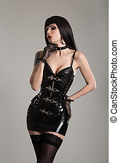 Sexy dominatrix woman in black leather corset