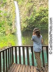 Woman talking on phone at waterfall
