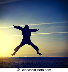 Man Silhouette jumping - Happy Man Silhouette jumping on the...