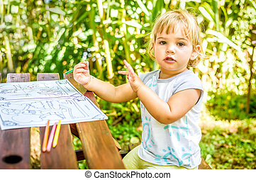 Beautiful Two year old girl drawing in a coloring book