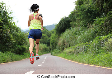 Runner athlete running on forest trail woman fitness jogging...