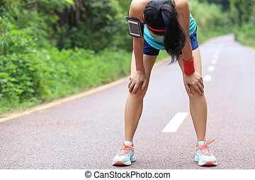 tired woman runner taking a rest after running hard on...