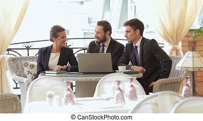 Three businesspeople eating snacks - Three businesspeople...