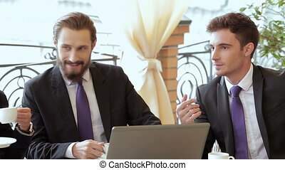 Two businessman meeting for lunch in coffee shop. Smiling...