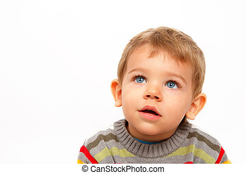 Boy in winter clothes looking up amazed
