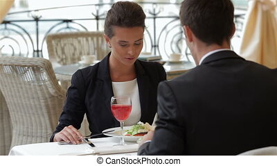 Businesswoman eating with a businessman during lunch....