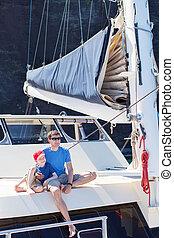 family at catamaran - family of two enjoying summer vacation...