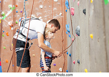 boy rock climbing - young father preparing his little son...