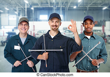 Car mechanic with tire wrench. - Smiling repairman with tire...