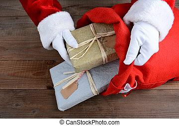 Santa Putting Packages in Bag - Closeup of Santa Claus...