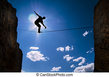 Concept of risk taking man balancing on the rope -...