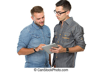 Two young man looking on a tablet pc, smiling