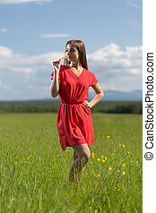 20 year-old girl in red dress sniffing a yellow flower in a...
