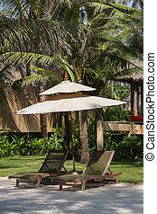 Tropical beach in Thailand - Two beach chairs, umbrella and...