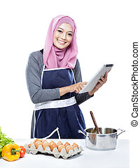 Beautiful young woman reading cooking recipe on tablet while...