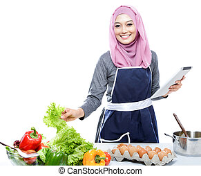 young woman reading cooking recipe on tablet while preparing...