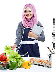 young woman wearing hijab reading cooking recipe on tablet...