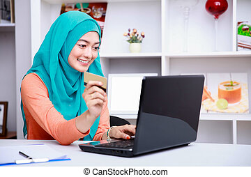 young muslim woman browsing internet on laptop while holding...