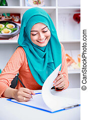 beautiful muslim woman writing on paper - portrait of...