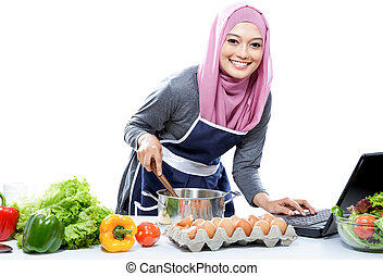 Young smiling woman wearing hijab cooking with reference the...