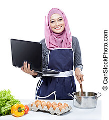 young smiling woman wearing hijab on laptop PC cooking...