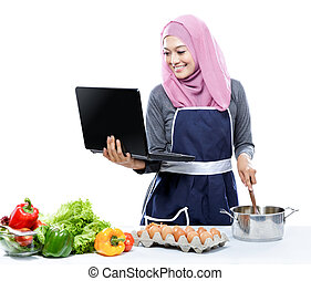 cooking young woman looking at laptop while preparing food