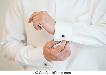 White shirt and cufflink - close up of a hand man how wears...