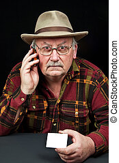 senior male with hat on phone with white card - photo senior...