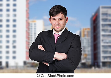 Businessman stands on the street in the city