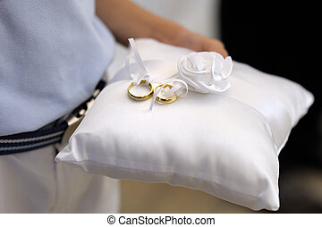Child holding a pillow with the wedding rings