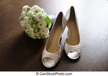 Brides shoes with a lucky coin and fowers