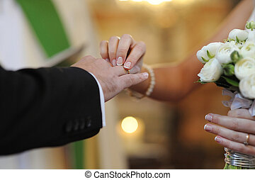 Bride putting a ring on groom\'s finger