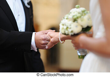 Bride and groom holding each other\'s hands during wedding...