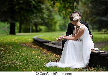 Bride and groom are sitting in autumn park - Bride and groom...