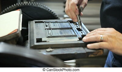printer tightens letterpress type in a chase - using a quoin...
