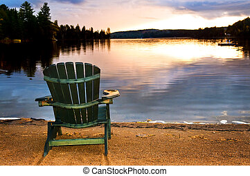 Wooden chair at sunset on beach - Wooden chair on beach of...