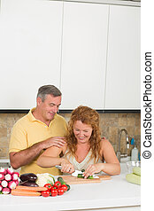 Middle-aged couple in the kitchen - Middle-aged man looking...