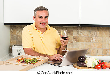 Mature man with laptop in the kitchen - Mature man holding a...