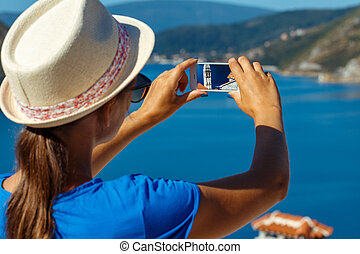 Girl in hat making photos of the smartphone Perast in Boka...
