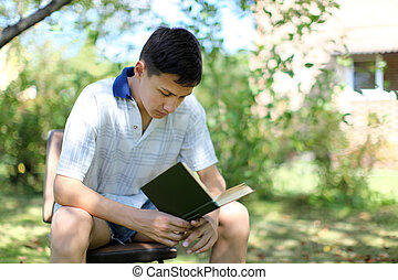 Young Boy Reading Book outdoors